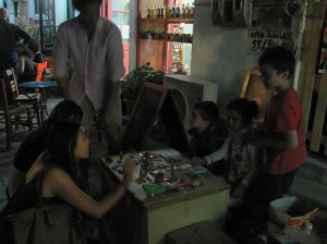 Children play store as their parents chat in nearby cafes.