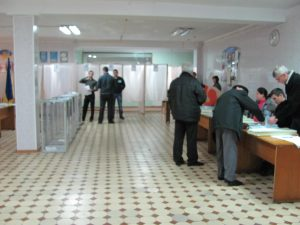 A well-organized voting station, with curtained voting booths and ballot boxes readily visible to prevent mischief.